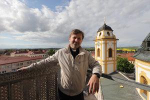 P. Tomáš Holcner s jednou z opravených věží kostela za zády.