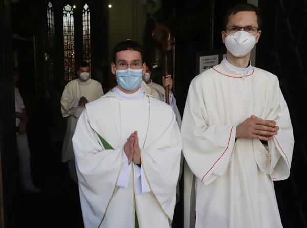 Novokněz Milan Werl a jáhen Josef Janoušek vychází z katedrály na Petrově.