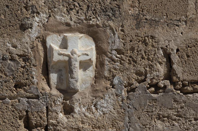 Na fasádě zničeného kostela se zachoval tento křížek