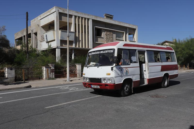 Zpustlými ulicemi projíždí mikrobus s turisty a průvodcem